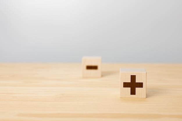 Voors en tegens concept kiezen voor plus met wazig min symbool concept van tegenstellingen hout blok