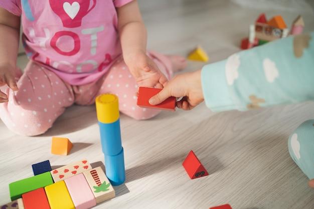 Voorschoolse spelletjes kinderen spelen met houten blokjes het kind passeert de rode kubus kinderen bouwen huizen
