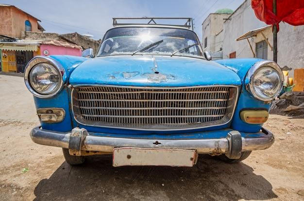 Voorste deel van een oude blauwe 60's auto zeer gebruikt op een onverharde weg.