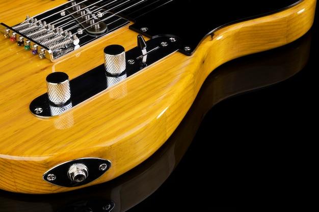 Voorste deel van het lichaam van een elektrische gitaar op zwart oppervlak.