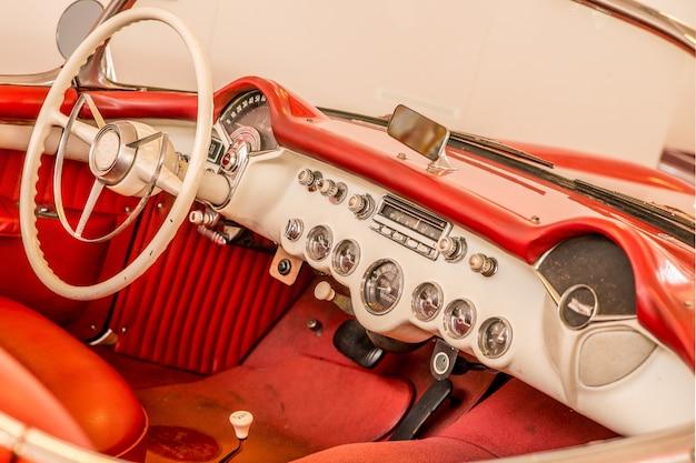 Voorste deel van het rode interieur van een auto, inclusief het witte stuur