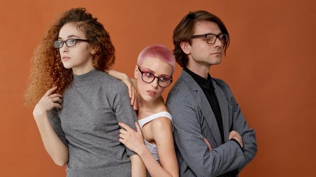 Voorste portret van drie jonge blanke stijlvolle modellen in vrijetijdskleding, bril dragen