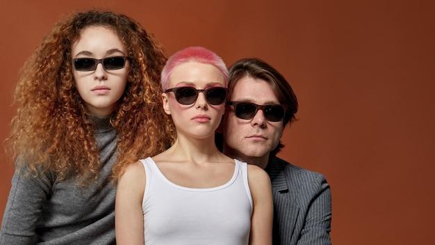 Voorste portret van drie jonge kaukasische stijlvolle modellen in vrijetijdskleding, zonnebril dragen