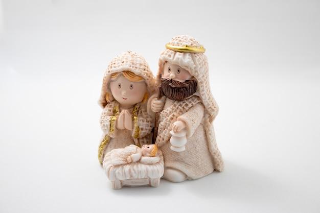 Voorstelling van een kerststal met de figuren van het kindje jezus, maria en jozef op een witte achtergrond.