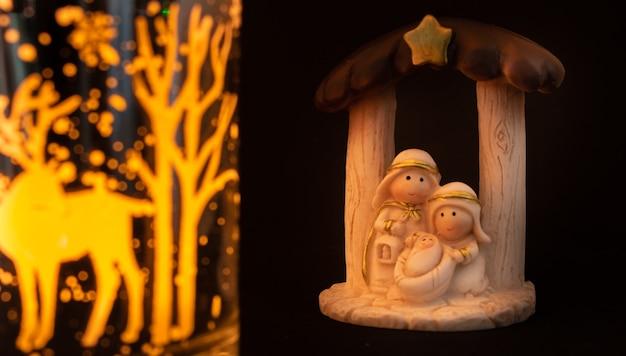 Voorstelling van een kerststal met de kleine figuren van het kindje jezus, maria en jozef op een zwarte achtergrond. kerst concept.