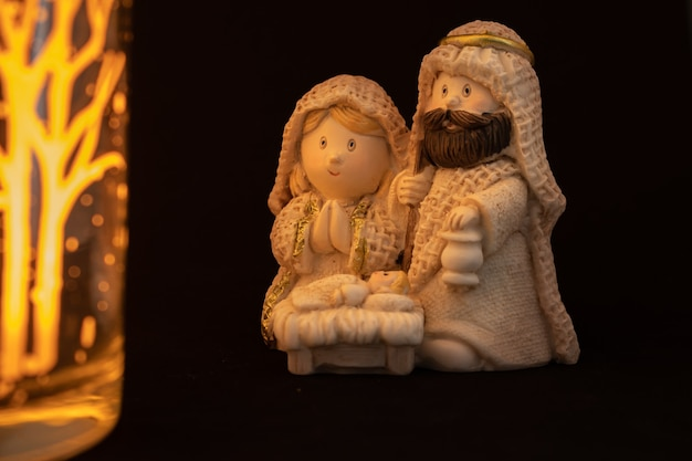 Voorstelling van een kerststal met de kleine figuren van het kindje jezus, maria en jozef op een zwarte achtergrond.