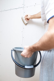 Voorstrijken van de muur met een borstel voor renovatiewerkzaamheden. voorbereiden van de muur voor het behangen.