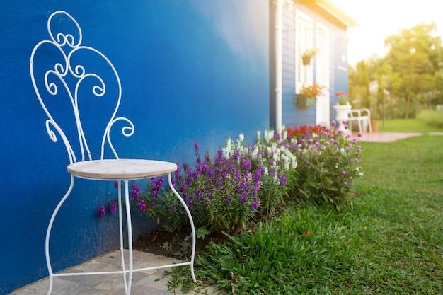 Voortuin van het huis met witte stoelen en kleurrijke bloemen met de achtermuur is blauw.