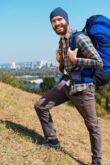 Vooruit en alleen vooruit! knappe jonge man die rugzak draagt en naar de camera kijkt met een glimlach