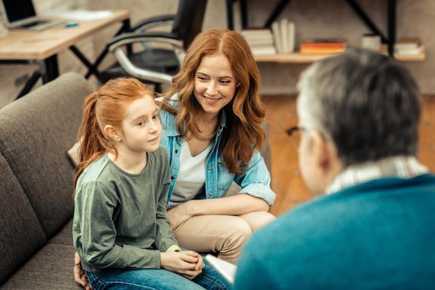 Vooruitgang in behandeling. vrolijke positieve vrouw die lacht terwijl ze naar haar dochter kijkt