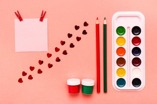 Voorwerpen voor het tekenen van een blad, potloden, gouache en aquarel op rood het concept is de liefde voor het tekenen van bovenaanzicht