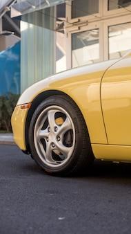 Voorwiel en bumper van een gele auto in de stad
