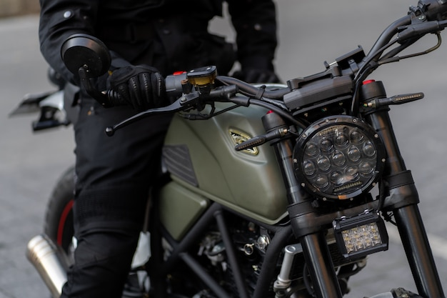 Voorwiel van de motorfiets met een trommelrem en een kabel er naar toe is de voorvork met een schokdemper en een veer. focus op een koplamp. retro motorfiets met koplamp.