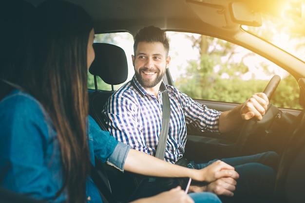 Voorzichtig rijden. mooie jonge paarzitting op de voorpassagierszetels en het glimlachen terwijl de knappe mens die een auto drijft.