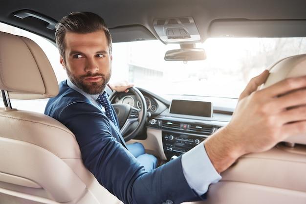 Voorzichtig rijden succesvolle jonge bebaarde zakenman in formele kleding rijdt naar een zakelijke bijeenkomst