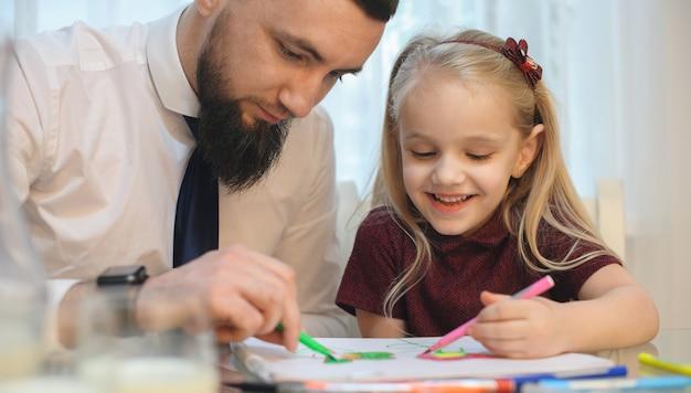 Voorzichtige blanke zakenman tekenen met zijn kleine meisje zittend aan tafel gekleed in een wit overhemd met stropdas