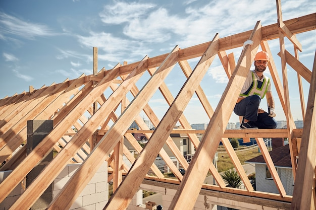 Voorzichtige bouwer met een veiligheidshelm en een goed zichtbaar vest die bovenop een houten huis werkt