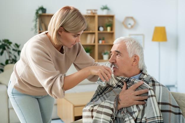 Voorzichtige jonge vrouw die voor haar zieke senior vader zorgt, gewikkeld in een plaid, terwijl ze hem een glas water geeft