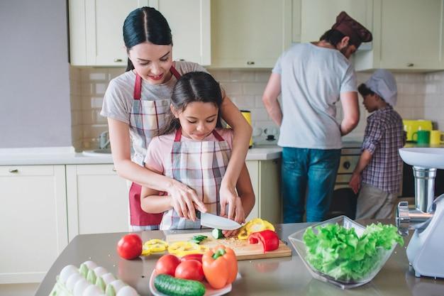 Voorzichtige moeder helpt haar kind groenten te snijden.