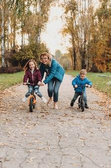 Voorzichtige moeder vermaakt zich met haar kinderen op de fietsen in het park