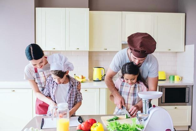 Voorzichtige ouders staan achter hun kinderen en helpen hen groenten te snijden.