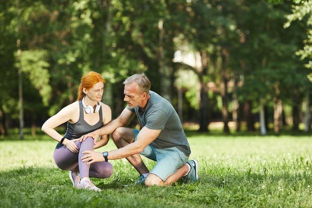 Voorzichtige volwassen fitnesstrainer knie van vrouw controleren terwijl ze pijn voelt na het sporten in het park