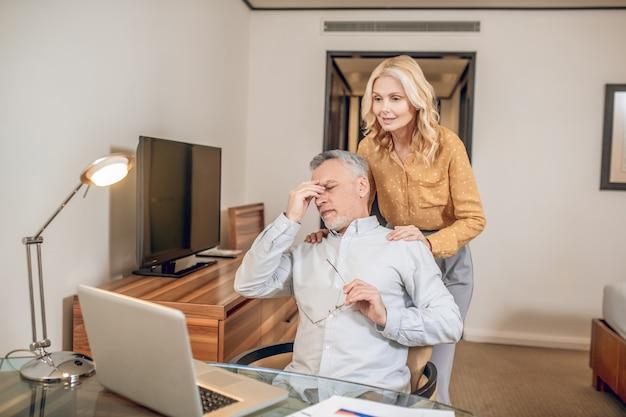 Voorzichtige vrouw. een man die thuis werkt en zich moe voelt, terwijl zijn vrouw hem steunt