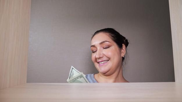 Voorzichtige vrouw komt om verborgen dollarbiljetten uit lade houten plank verre hoek te halen, glimlacht in inloopkast thuis dichtbij zicht van rek