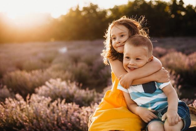 Voorzichtige zus omhelst haar kleine broer terwijl poseren tegen de zon met een lavendelveld op de achtergrond