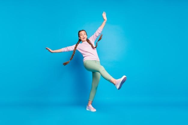 Voorzichtigheid! gladde vloer! volle lengte foto van bang meisje gaan lopen slip vallen schreeuw omg verhogen been handen voelen paniek dragen casual stijl outfit geïsoleerd over blauwe kleur achtergrond