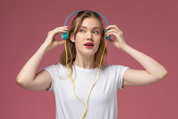 Voorzijde sluiten jonge aantrekkelijke vrouw luisteren naar muziek via oortelefoons op de roze muur model kleur vrouwelijke jong