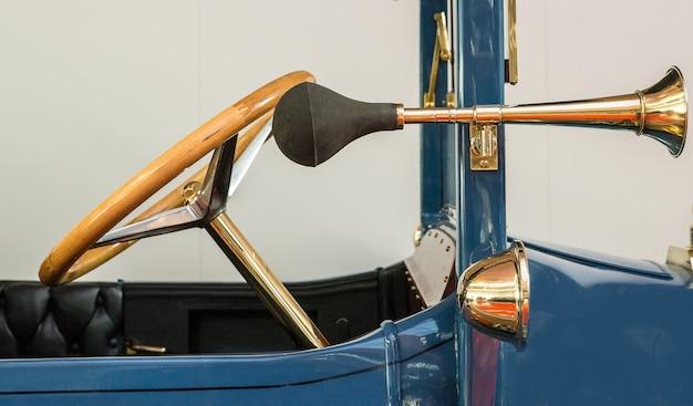 Voorzijde van een vintage blauwe auto met een antiek gouden stuur en een aparte toeter