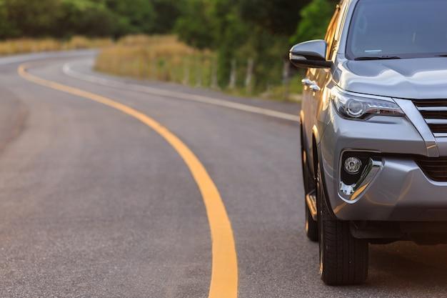 Voorzijde van nieuw zilveren suv-autoparkeren op de asfaltweg
