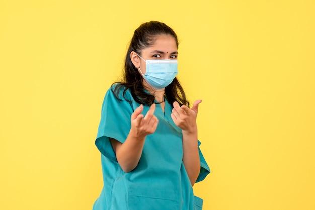 Voorzijde vie vrouwelijke arts met masker dat met vingers aan voorzijde richt