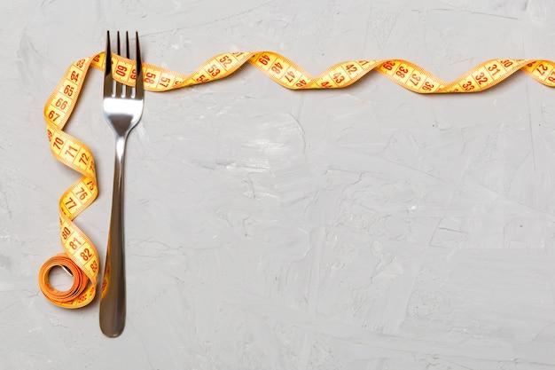 Vork en gekrulde meetlint dieet concept met kopie ruimte