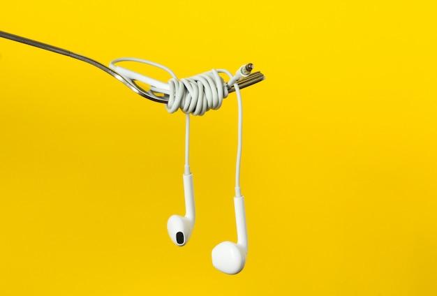 Vork en hoofdtelefoons op een gele achtergrond, close-up