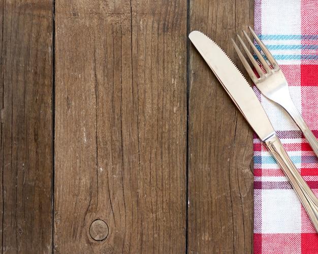 Vork en mes op keukenhanddoek en de oude houten mening van de lijstbovenkant met exemplaarruimte