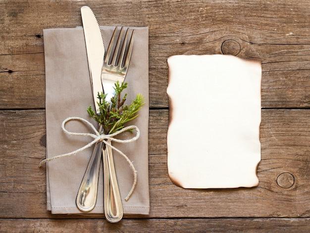 Vork en mes op servet en oude houten tafelblad bekijken met kopie ruimte