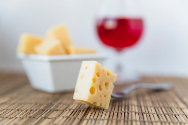 Vork in de buurt van set van verse kaas in schotel en een glas wijn op tafel