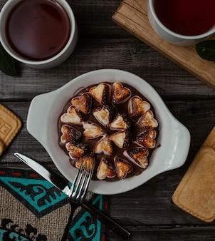 Vork klaar om een van een fijn gekookt hartvormige koekjes uit een witte schotel te plukken