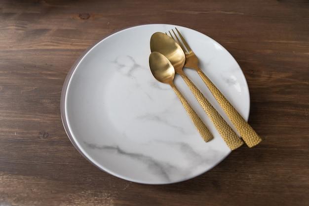 Vork, lepel en plaat op houten tafel in restaurant. marmer plaat, gouden mes, vork en lepel op houten achtergrond. schotels en bestek, plaat met lepels en vork. koken concept. kopie ruimte