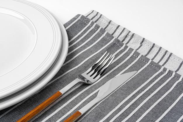 Vork, mes en bord op handdoek. geïsoleerd op witte achtergrond. detailopname.