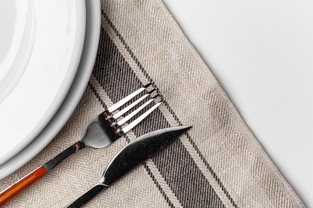 Vork, mes en bord op handdoek. geïsoleerd op witte achtergrond. detailopname. Premium Foto