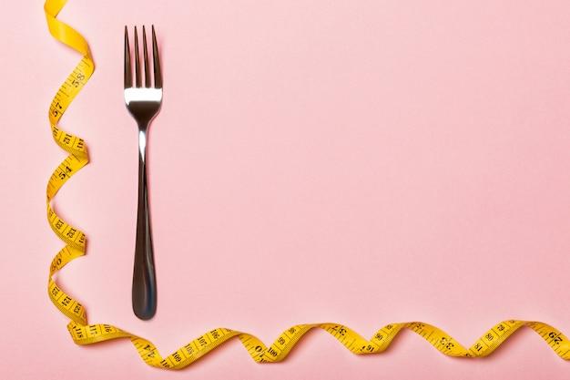 Vork met gekruld meetlint. bovenaanzicht van ftatware. dieetconcept met ruimte voor uw ontwerp