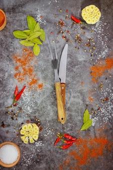 Vork met mes en kruiden op donkere achtergrond. bovenaanzicht.