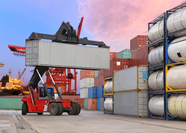 Vorkheftruck die de containerdoos behandelen bij werf met havenachtergrond