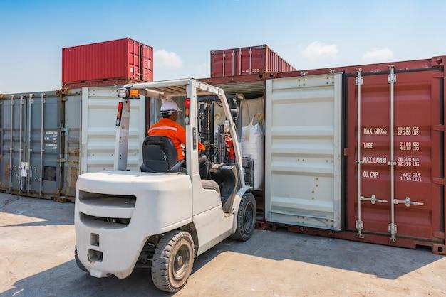 Vorkheftruck die goederen laden aan containerdoos in pakhuisgebied
