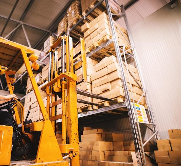 Vorkheftruck nadert pallet gevuld met stapels dozen op een rek in opslagruimte.