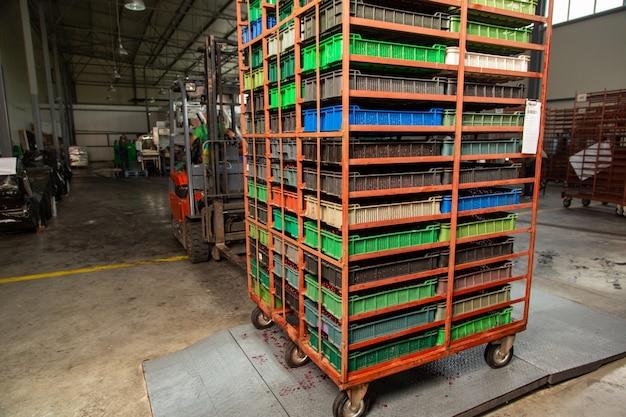 Vorkheftruckchauffeur zet een stapel dozen met kersen op magazijnweegschalen voordat hij in de vrachtwagen laadt.