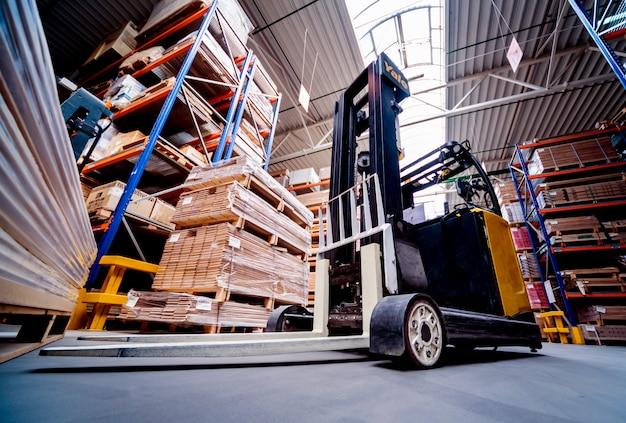 Vorkheftrucklader in het scheepswerf van het opslagpakhuis. distributieproducten. levering. logistiek. vervoer.